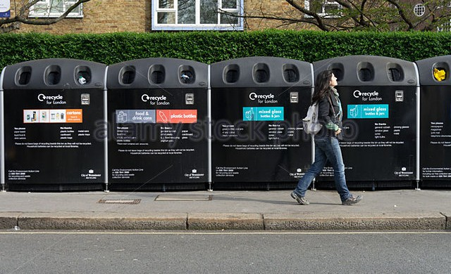 young-woman-walking-by-a-row-of-recycle-bins-london-england-uk-c2fh3h